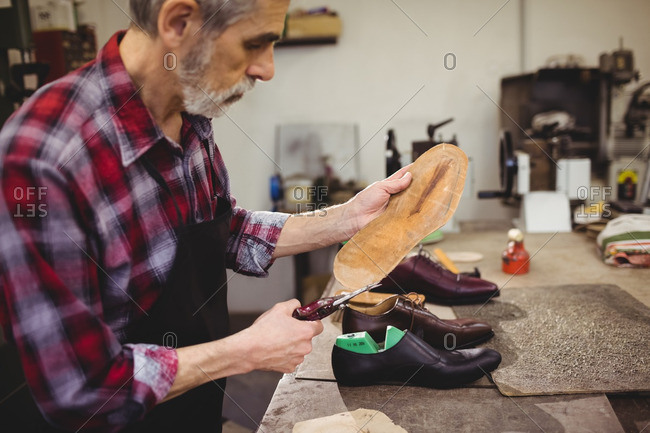 Profile view of cobbler cutting the sole of a shoe in his workshop
