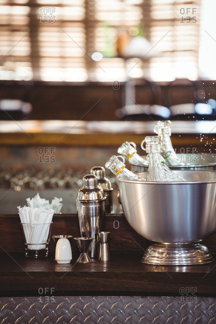 Bottles of cocktail in ice buckets on bar counter at bar