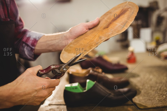 Close up of hands cutting the sole of a shoe in a workshop