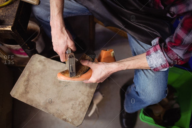 Overhead of cobbler stapling a shoe in his workshop