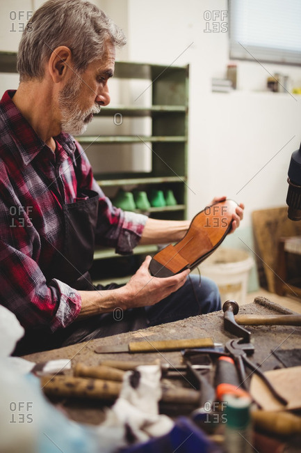 Profile view of cobbler looking the sole of a shoe in his workshop