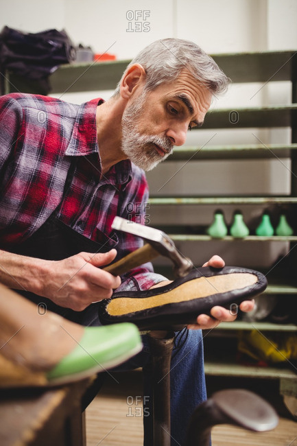 Side view of cobbler hammering on the sole of a shoe in his workshop