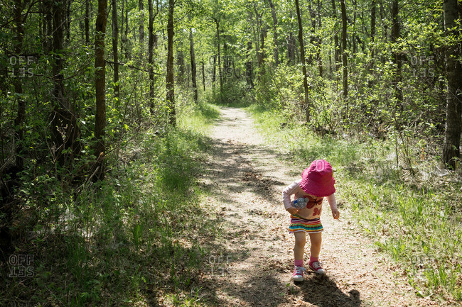 Little girl walking on path in the woods