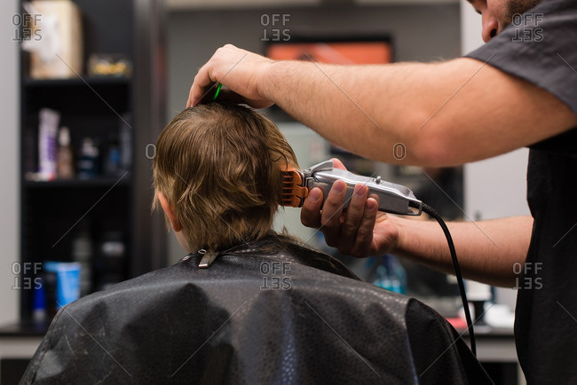 Boy getting haircut with clippers at a barbershop