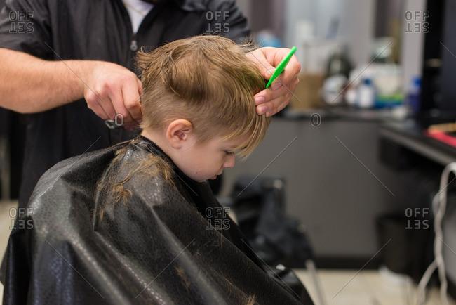 Boy Getting Haircut At A Barbershop Stock Photo
