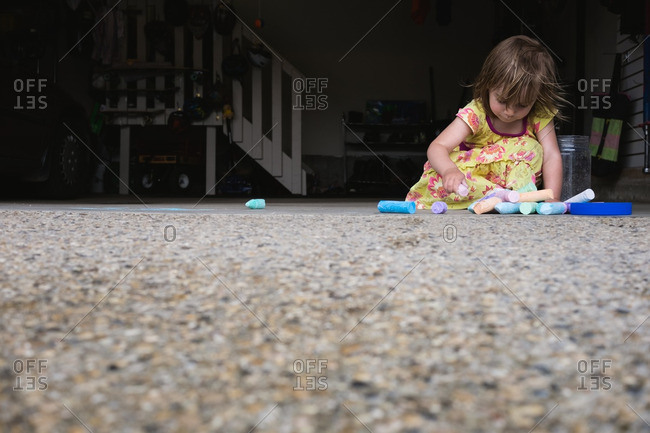 Little girl coloring in a garage with sidewalk chalk