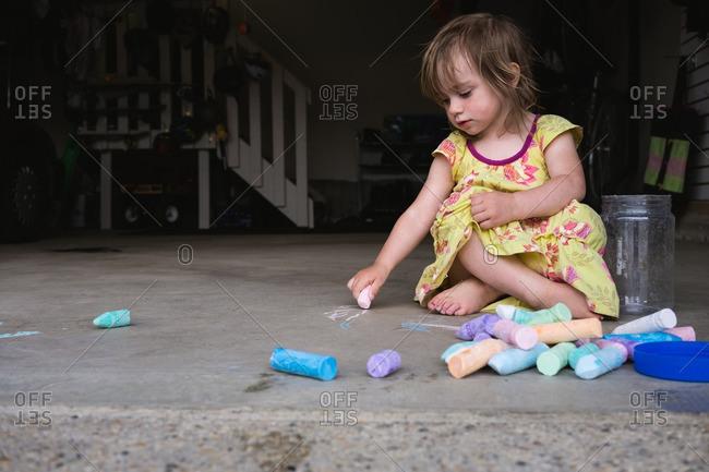 Little girl drawing in a garage with sidewalk chalk