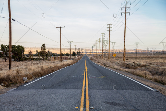 Power lines line an empty road in the Mojave Desert outside Lancaster, California