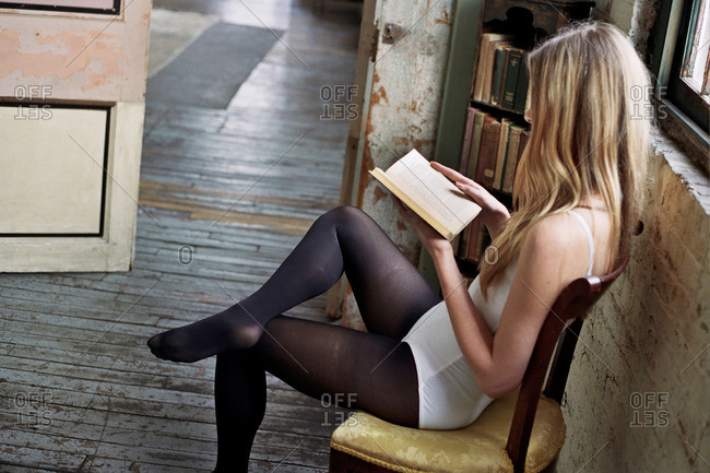 Woman in undergarments reading a book in a rundown house