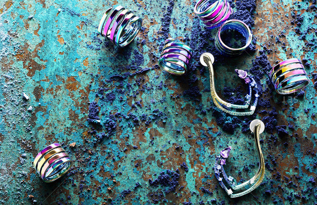 Iridescent rings and earrings and teal powder dye