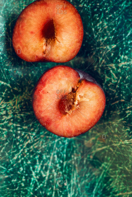 Halved plum on a teal surface