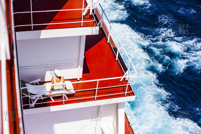 Passenger relaxing in a sun chair onboard a container ship in the red sea