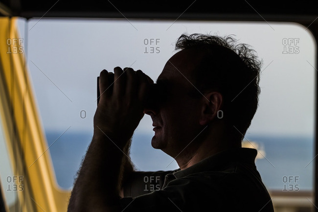 April 17, 2014: Officer of a container ship looking through binoculars