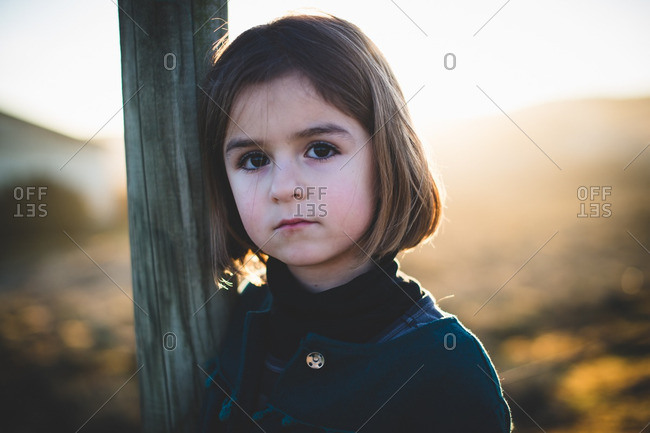Portrait of a little girl leaning against a wooden post
