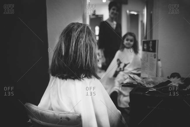 Little girl looking in mirror after having her hair cut at a salon