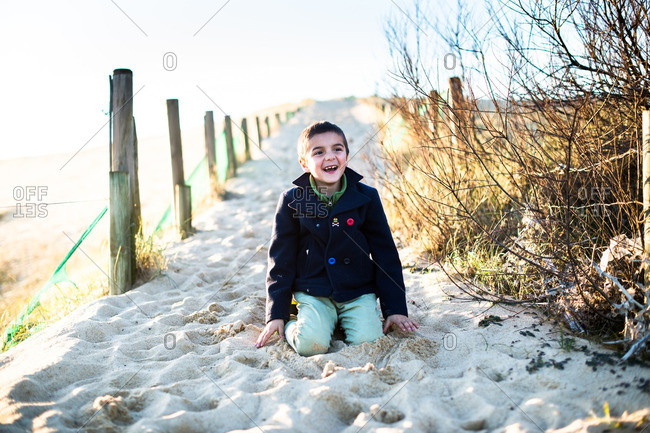 Little boy sitting in the sand wearing jacket