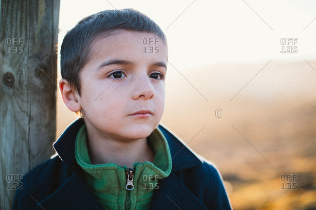 Portrait of a little boy leaning against a wooden post