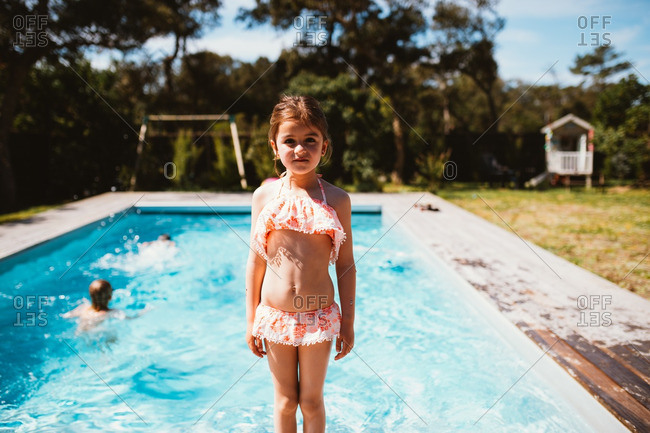 Little girl standing by a pool