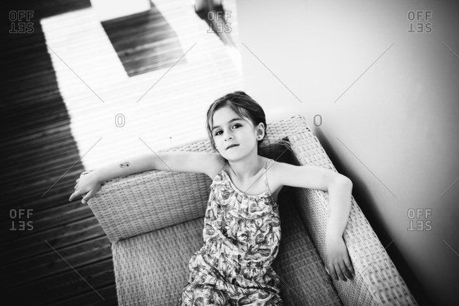 Little girl relaxing on a whicker sofa
