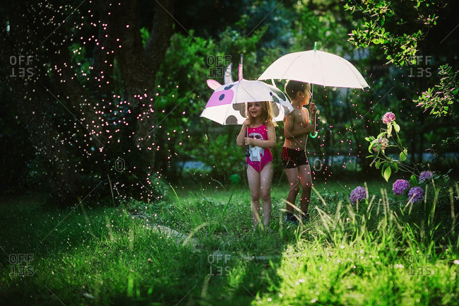 Children playing with umbrella and a sprinkler