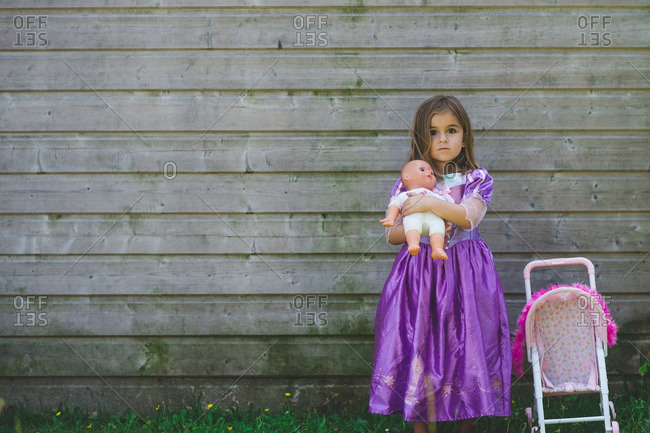 Little girl in purple dress playing with baby doll