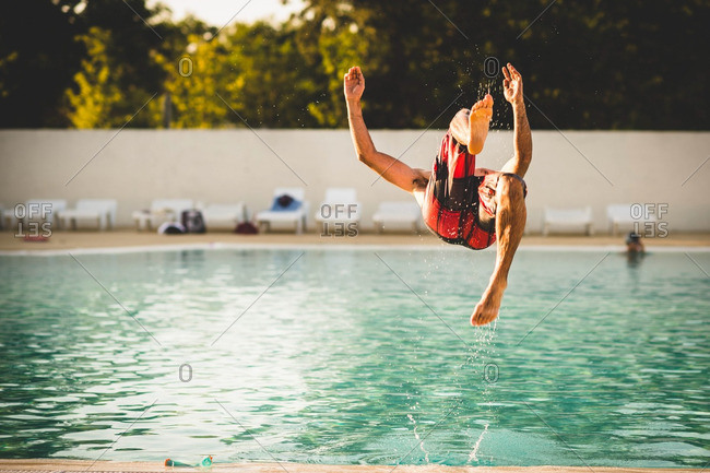 Man doing back flip into swimming pool