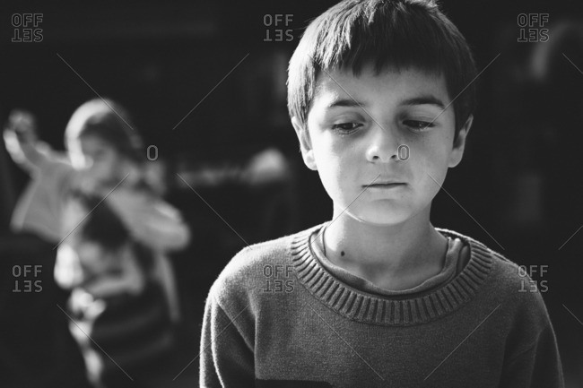 Portrait of a little boy looking away in black and white