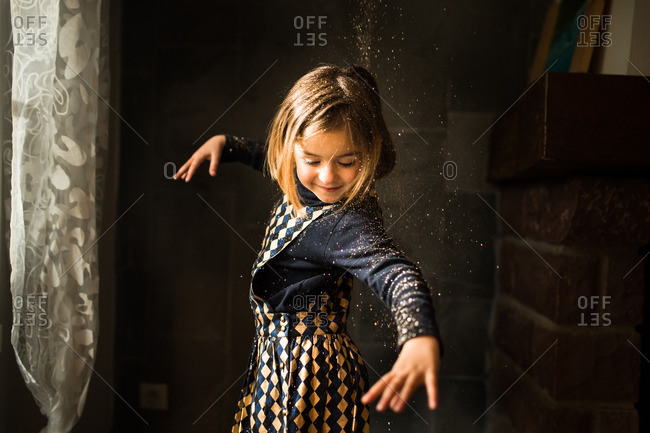 Little girl dancing around throwing glitter in the air