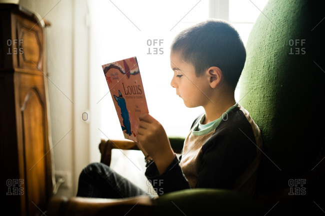 Boy sitting in chair reading a book