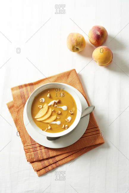 Bowl of chilled peach soup on orange napkin