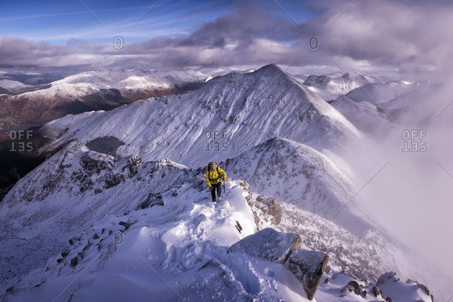 Mountaineer in yellow jacket in winter