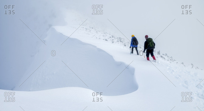 Two people mountaineering in deep snow