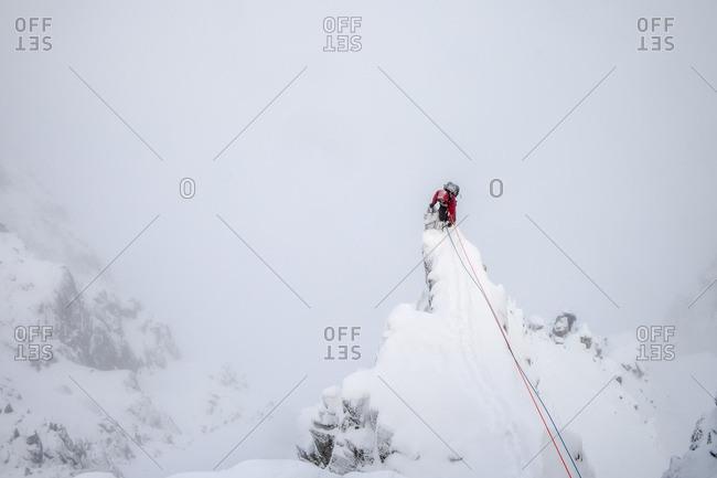Mountaineer climbing up spire in winter