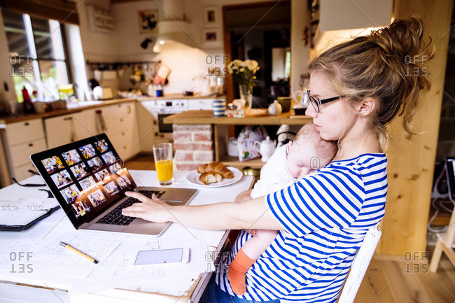 Mother with baby at home working with laptop