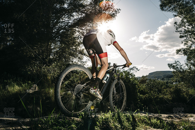 Mountain biker on the move in backlight