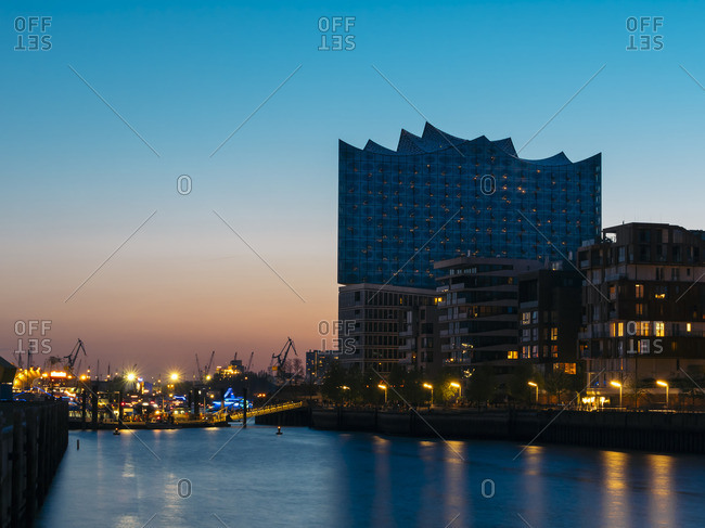 Elbphilharmonie with multi-family houses in the foreground at blue hour