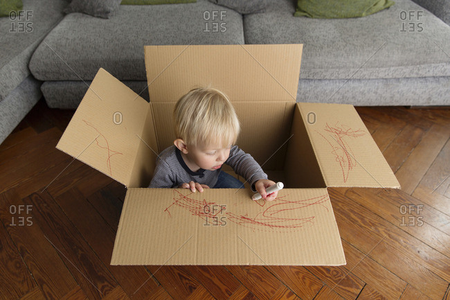 Toddler sitting in a cardboard box painting with a red marker