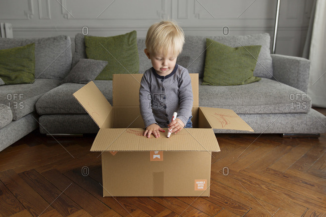 Toddler standing in a cardboard box drawing with a red marker
