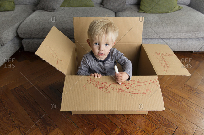 Portrait of toddler in a cardboard box drawing with a red marker