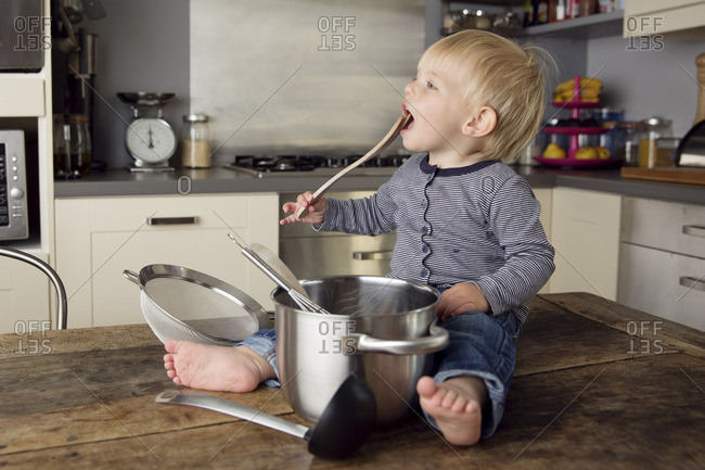 Toddler sitting on the kitchen table playing with kitchen utensils