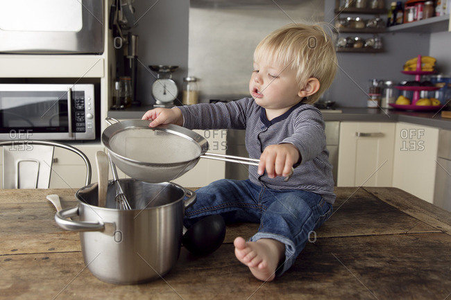 Toddler boy sitting on the kitchen table playing with kitchen utensils