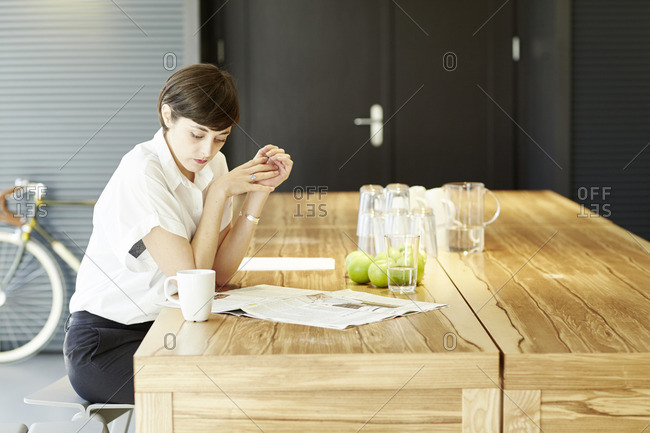 Woman reading newspaper at wooden table in a modern canteen
