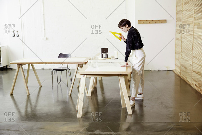Architect in an office standing over a drafting table