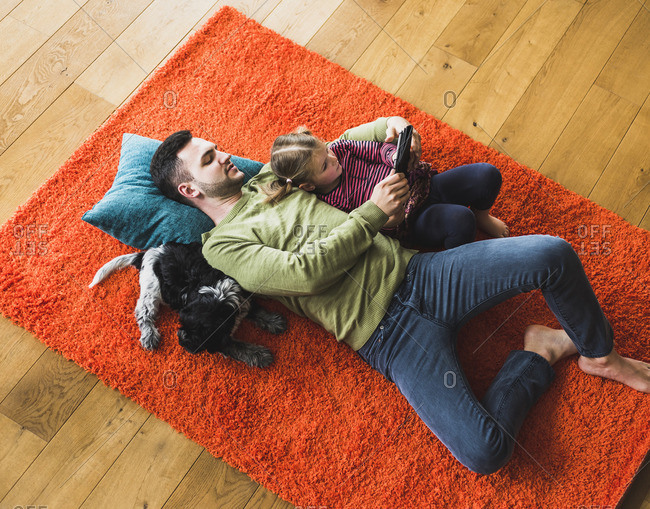 Dad and daughter lying on carpet on the floor using digital tablet