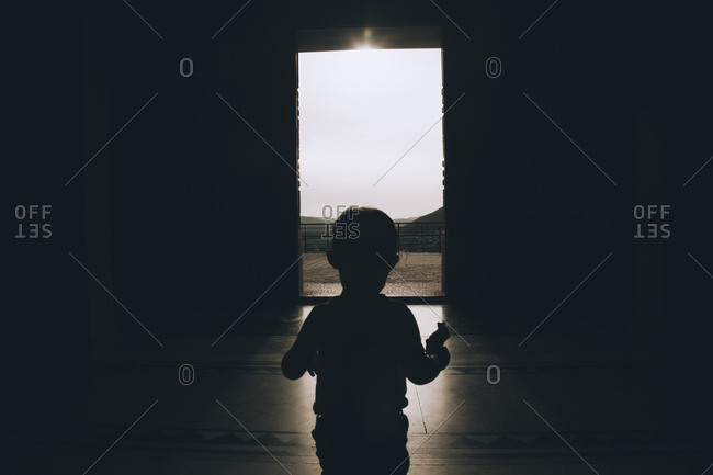Silhouette of little boy walking to exit of a house