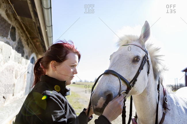 Side view of woman holding bridle while looking at horse