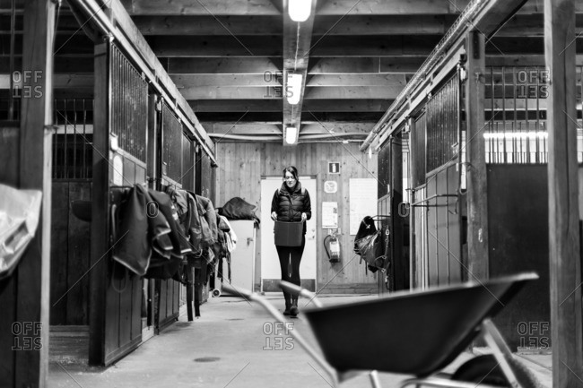 Woman carrying bucket while walking in stable