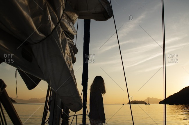 Rear view of woman standing by boat mast on sea during sunset