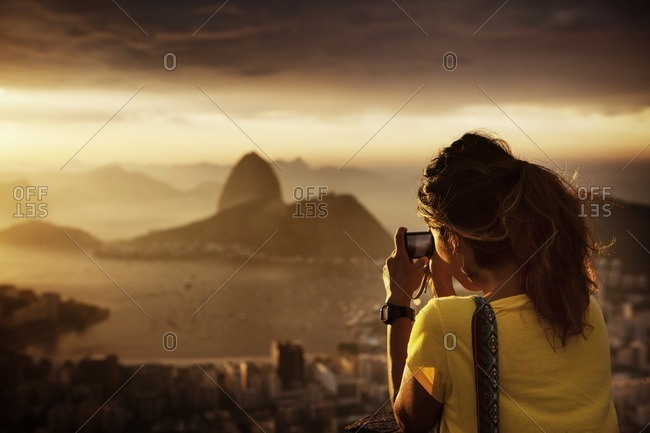 Rear view of woman photographing Guanabara Bay during sunset