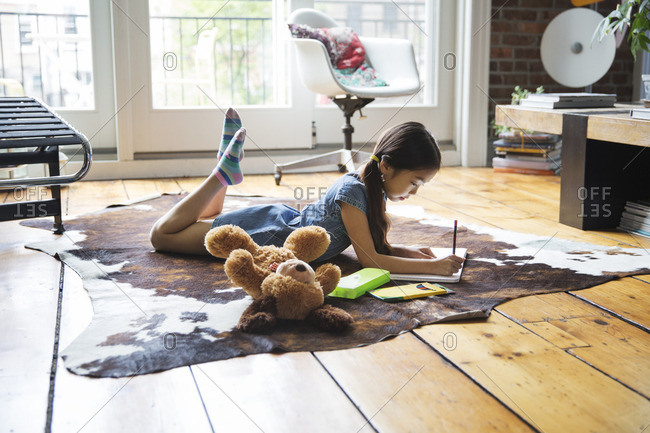 Girl lying on carpet and writing on book at home